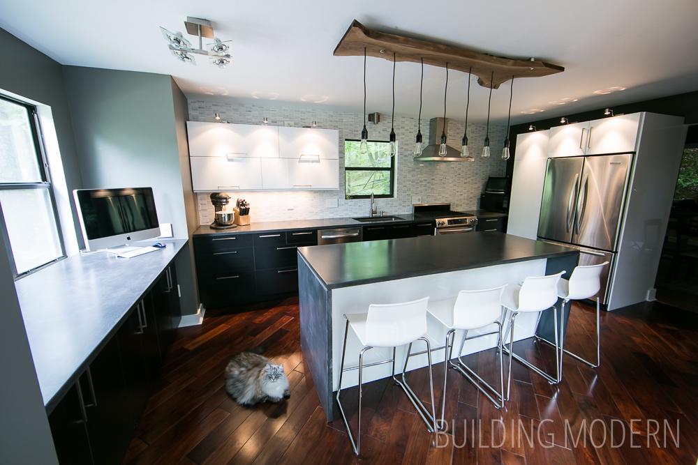 Modern Ikea kitchen with walnut floors concrete countertops marble backsplash