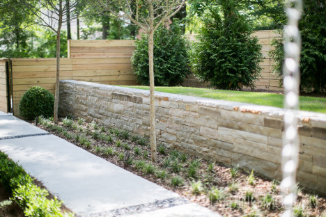 Stone retaining wall with wooden fence