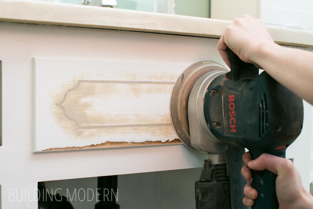 sanding a cabinet with a Bosch sander